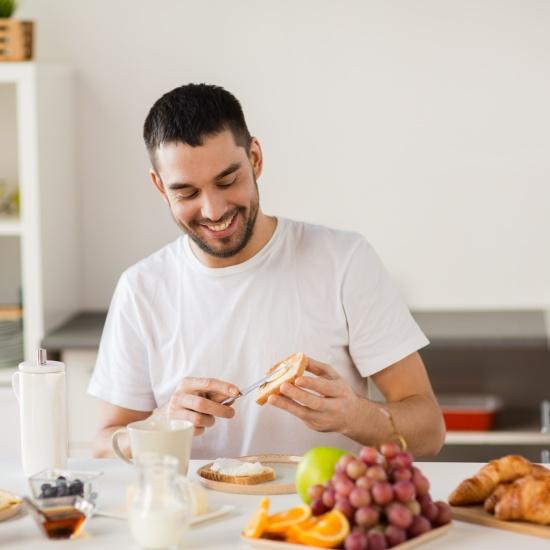 Der Mann lacht beim Zubereiten eines gesunden Frühstücks.